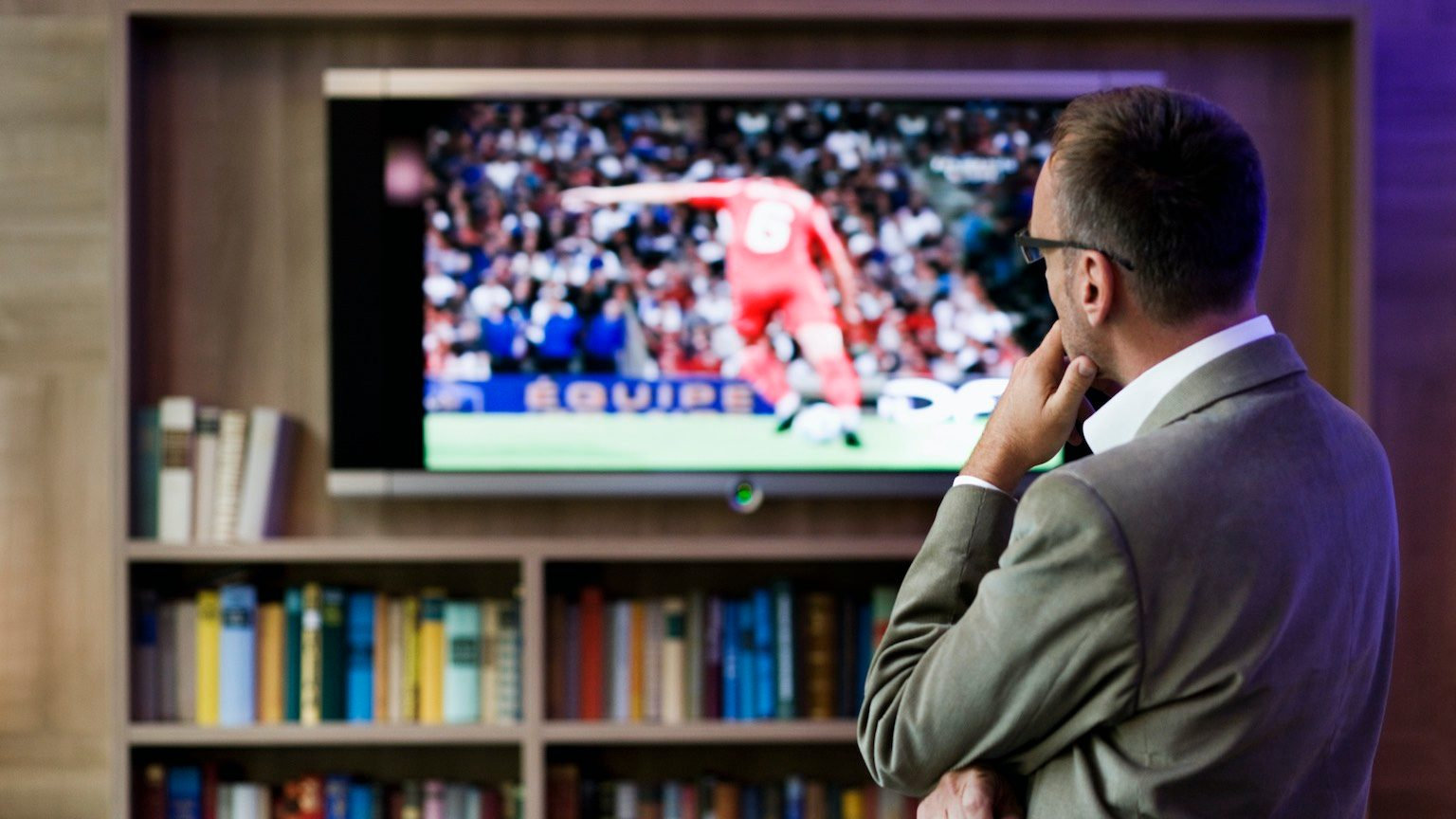 Man watching soccer on flat panel television