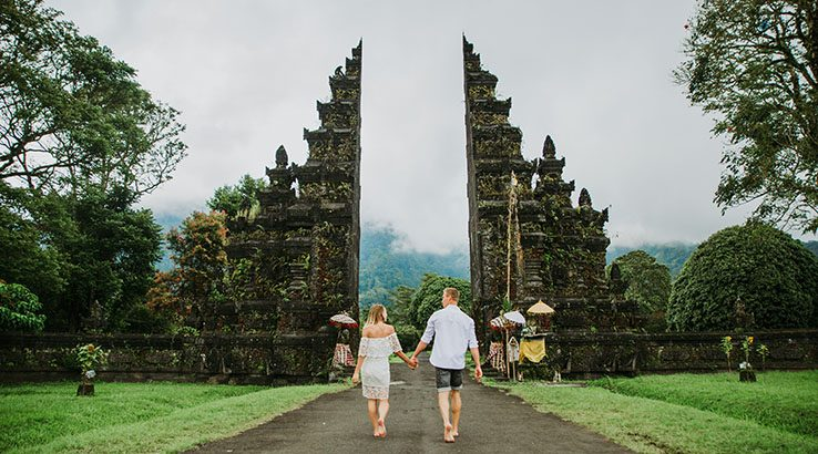 Couple Walking On Footpath At Gate Against Sky