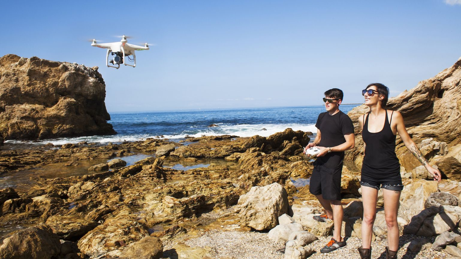 A young couple flying a drone at a rocky beach