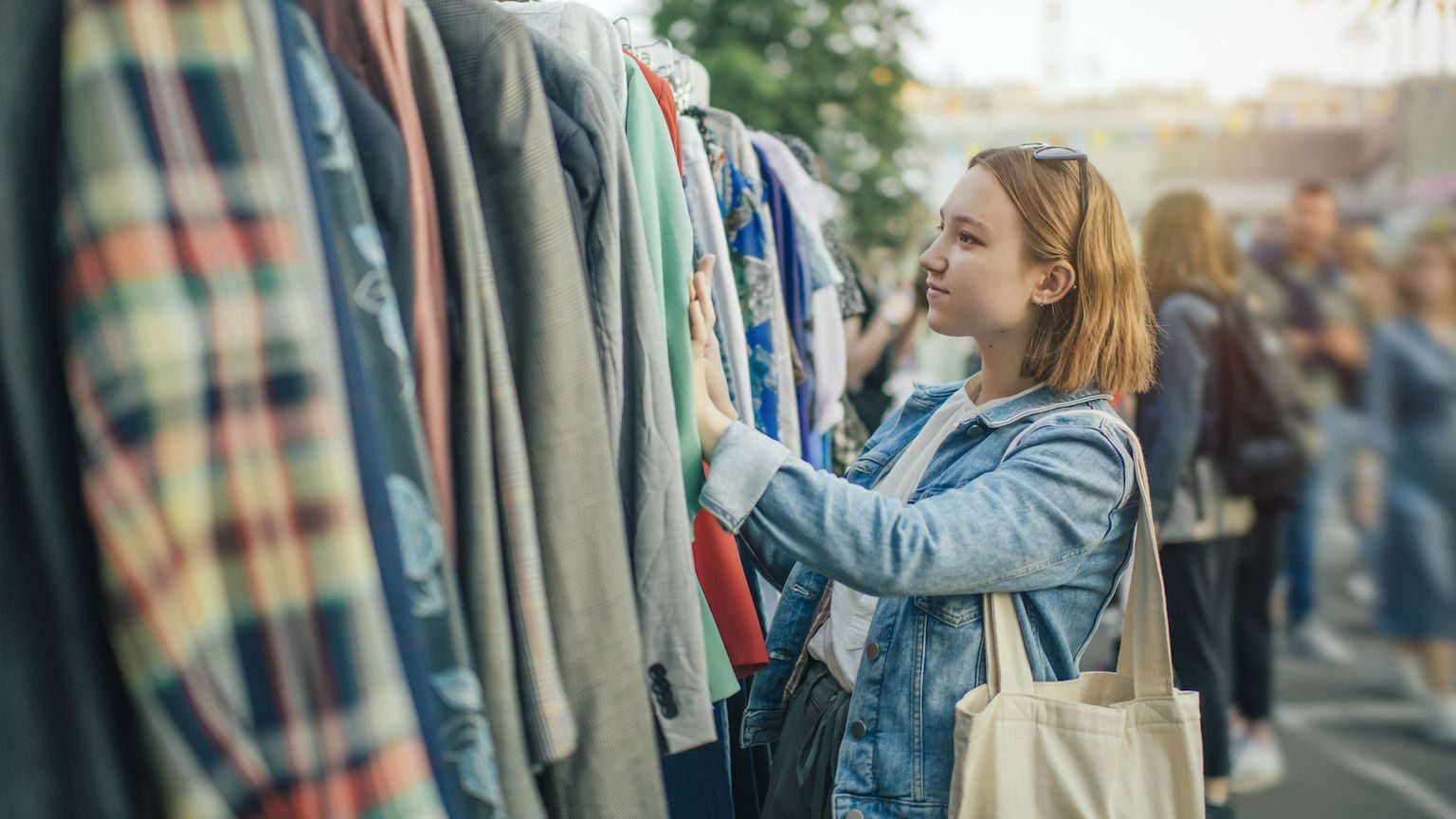 A young woman browsing a second-hand clothing rack at an outdoor market