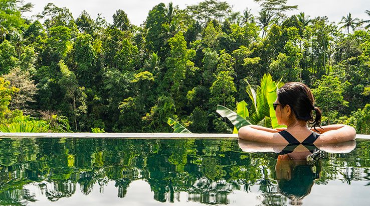 Woman enjoying view in infinity pool, Ubud, Bali, Indonesia