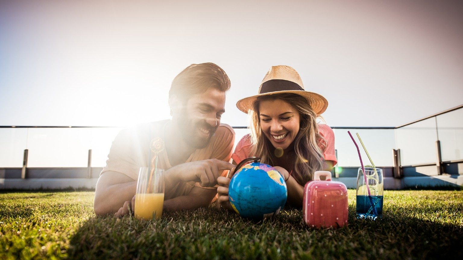 A couple on a lawn, looking at a globe and sipping cocktails.