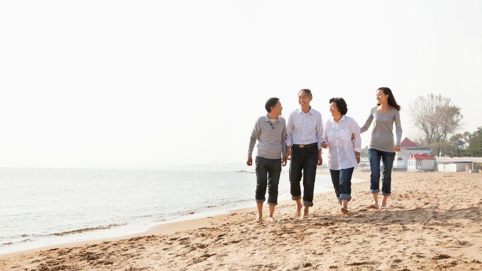 Multi-generational family walking on the beach.