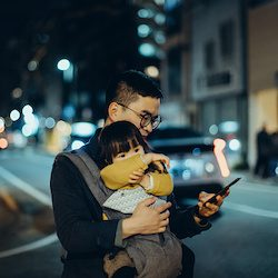 Young Asian father with cute little daughter using mobile app on smartphone to arrange taxi ride in downtown city street, with blurry traffic scene as background