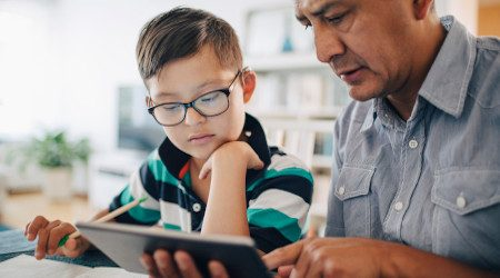 Father showing digital tablet to son while studying at table