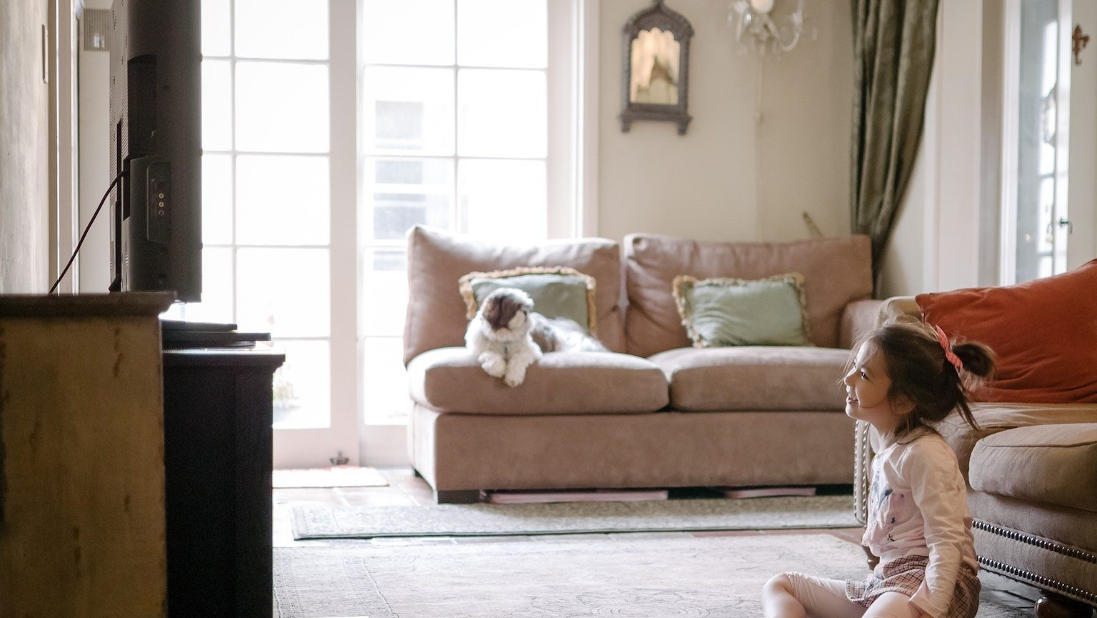 A little girl is watching TV. She's playing a movie and appears happy and entertained by what's playing on the LCD TV. She's 6 years old and Eurasian. Her dog is sitting on the couch in the background. The home's interior appears stylish and includes old-world/vintage home decor.