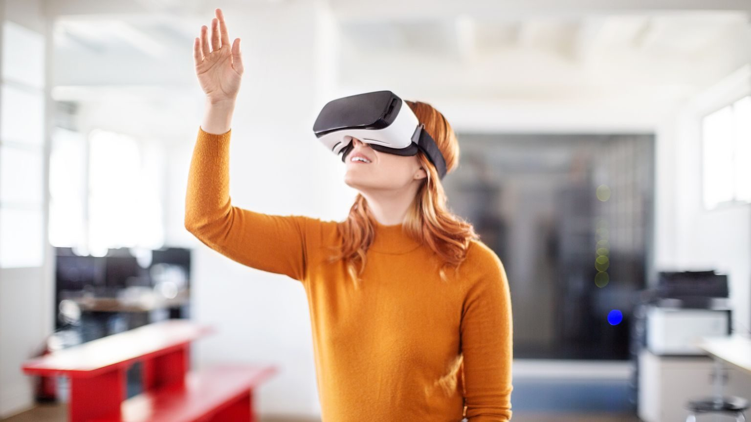 Woman wearing a virtual reality headset in her office