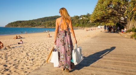 Sole Woman walking along the beach with shopping bags