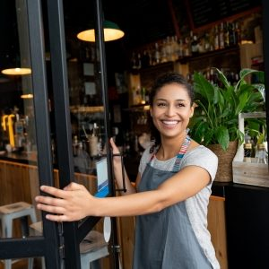 Happy business owner opening the door at a cafe