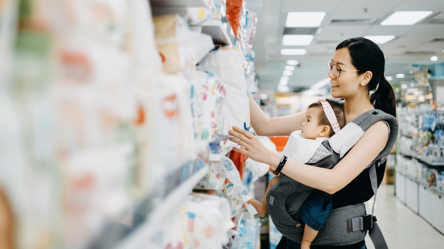 Young Asian mother carrying cute baby girl shopping for baby product in a shopping mall and is looking at a variety of diapers