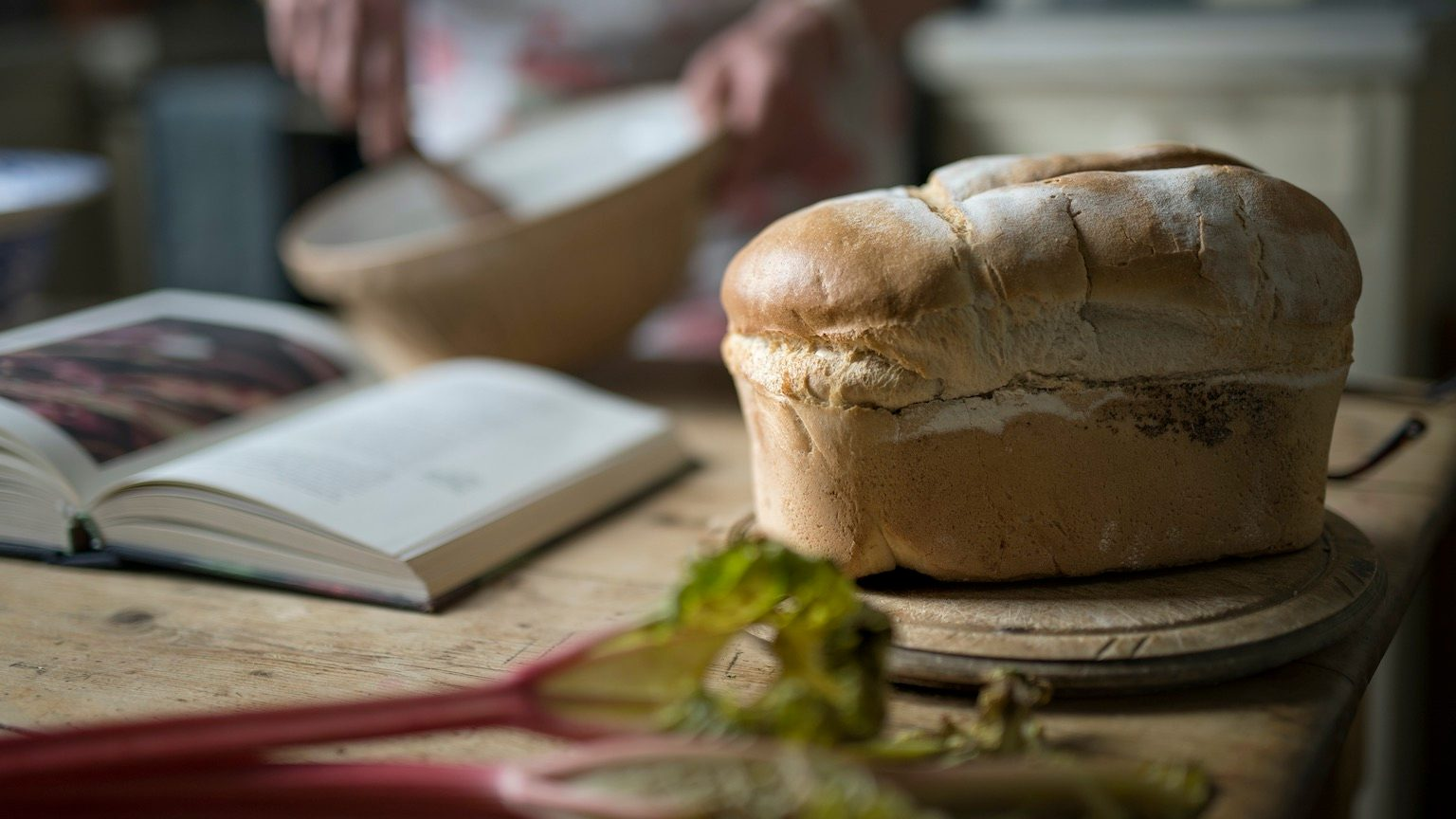 a fresh homemade loaf of bread in a rustic kitchen with a person cooking in the background.