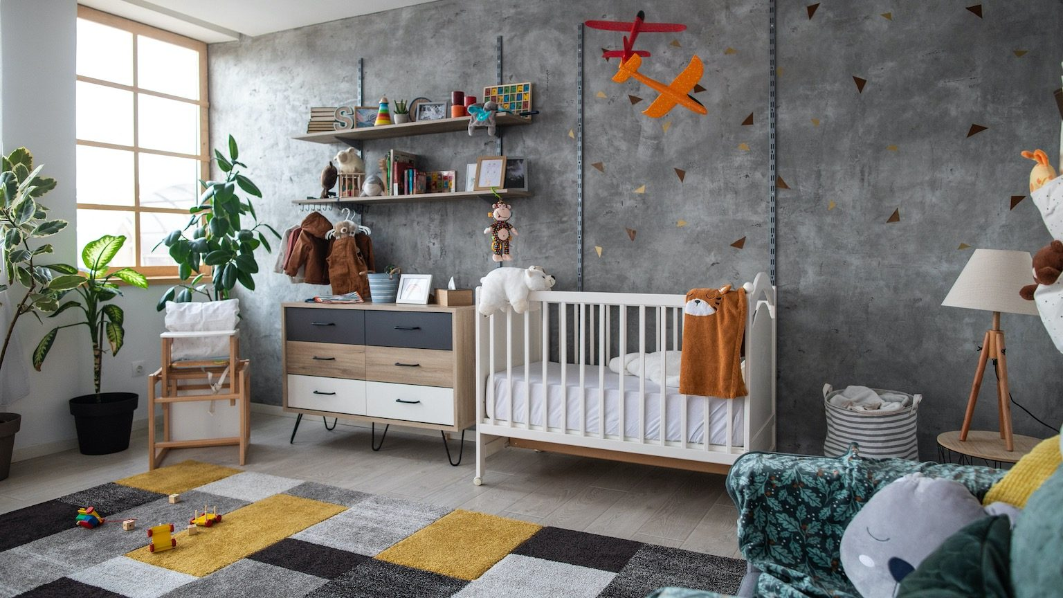 Empty children's playroom with crib, toy planes, plants, furniture