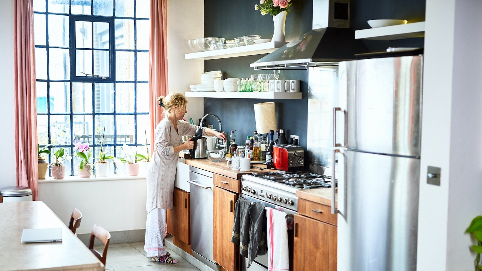 Woman wearing pyjamas making tea on weekend, relaxation, morning routine, domestic life