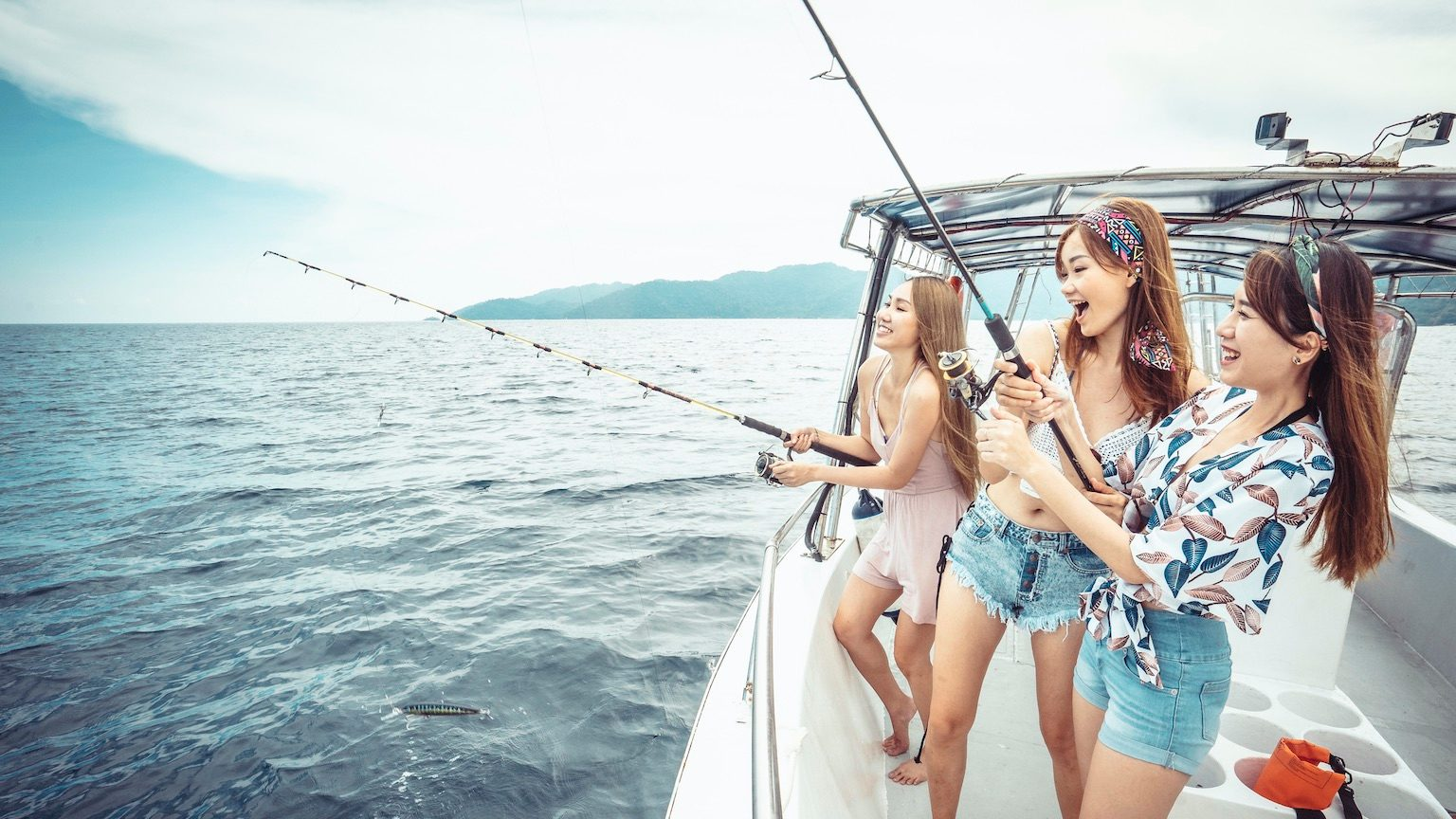 3 young teenage girls fishing on a boat in the middle of the ocean