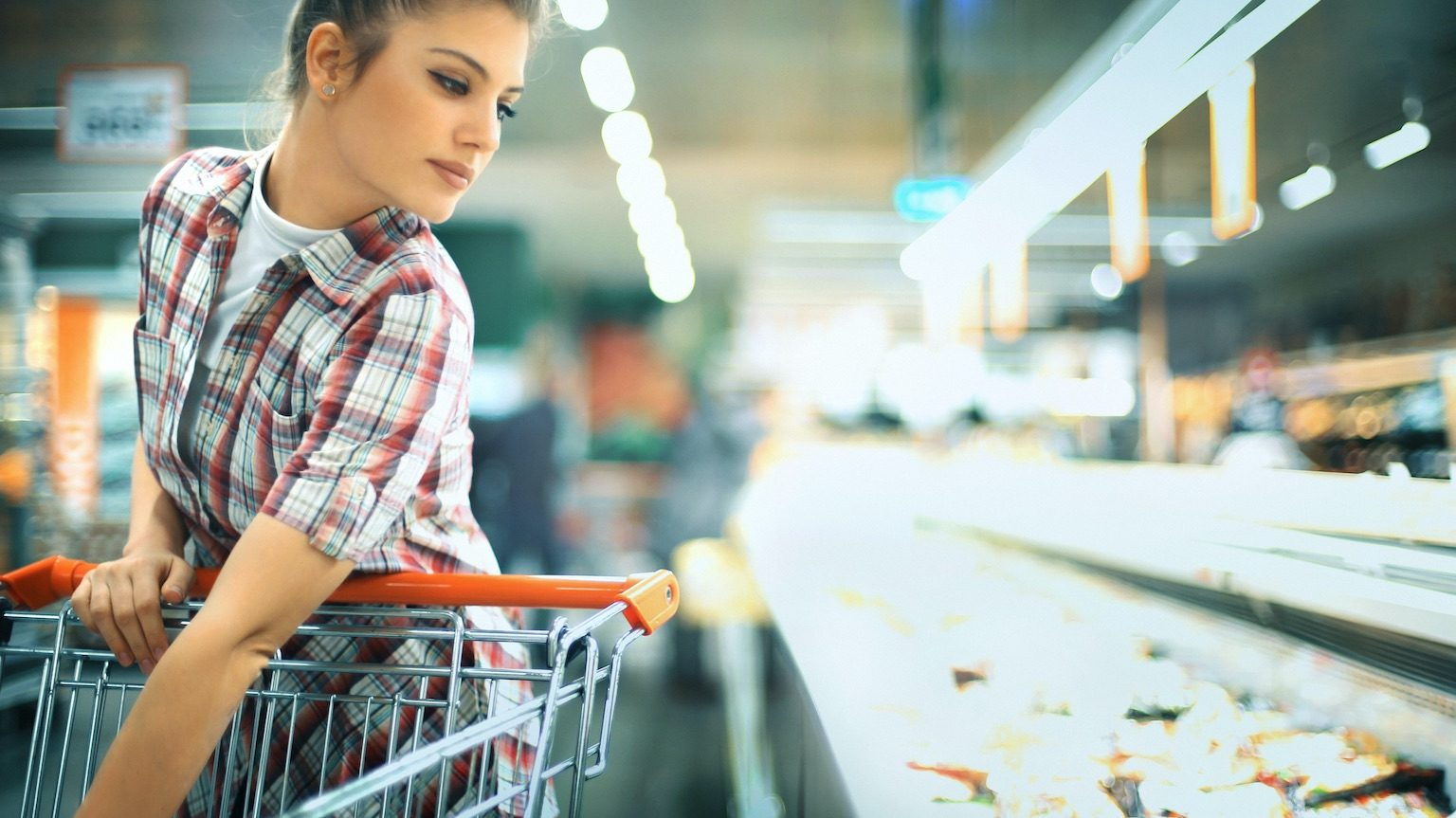 Closeup of mid 20's blond woman doing her weekly shopping at local supermarket. She's at refrigerated section and just put a certain product into her cart.