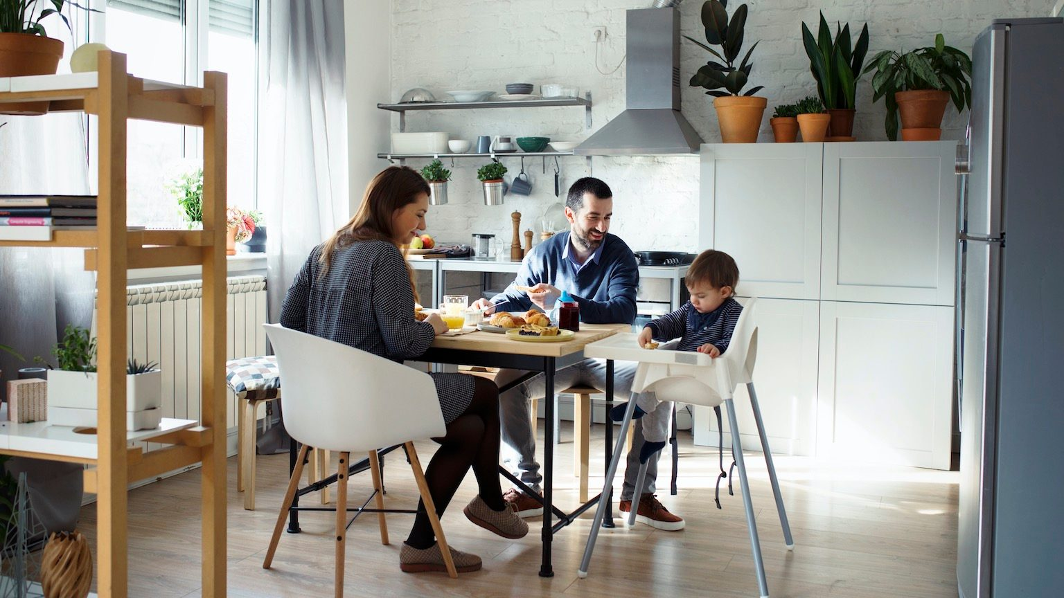 Parents looking at son sitting on high chair while having breakfast in kitchen
