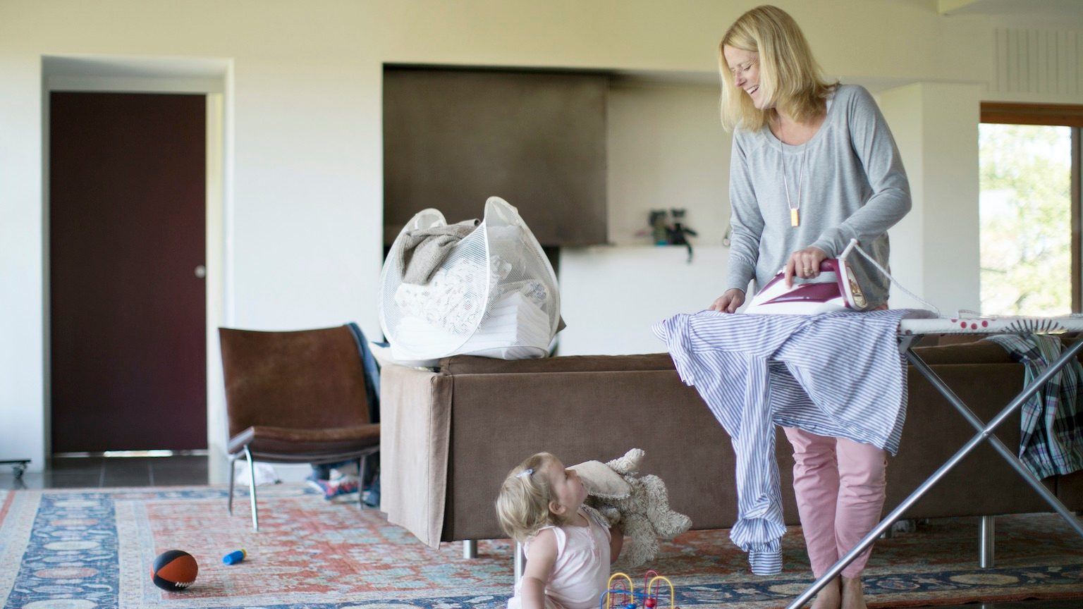 Mother ironing laughing at toddler (18-24 months) on floor