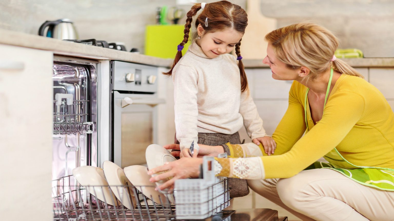 Mother And Daughter Using Dishwasher