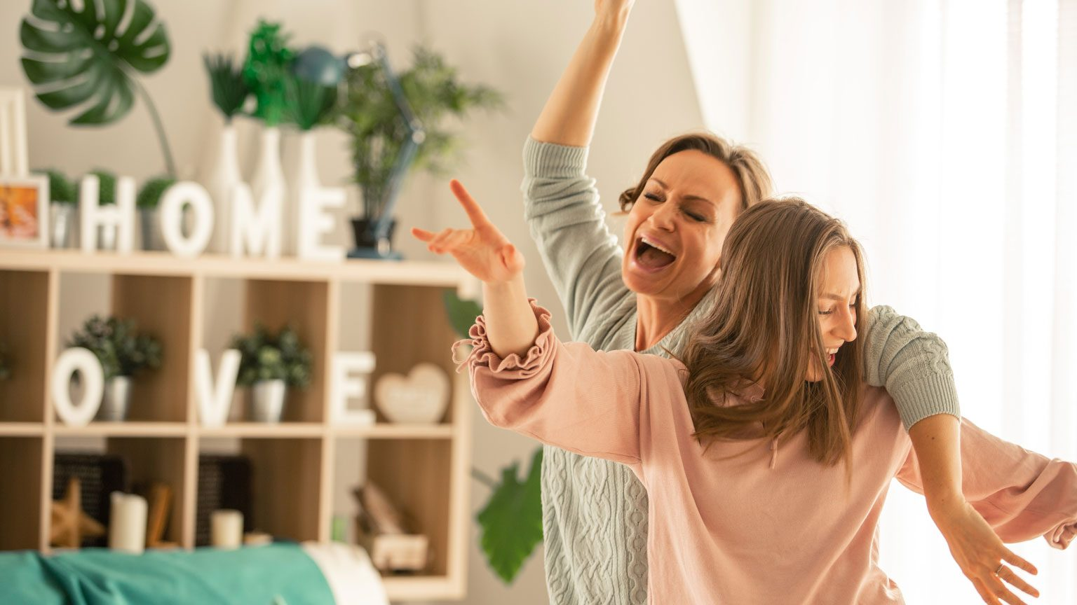 Mother and her daughter captured in the moment of pure joy and laughter while dancing and singing together in their living room.