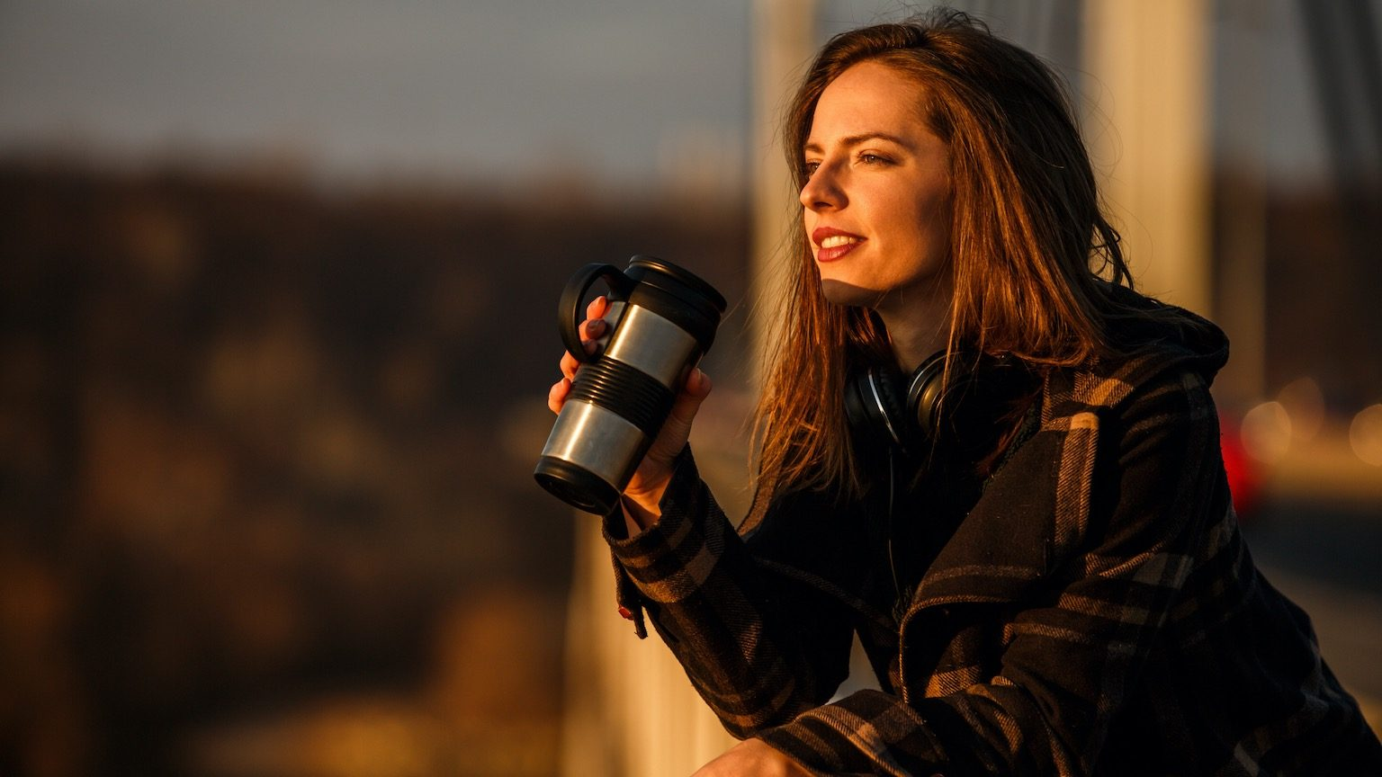 Young brunette woman holding thermos cup, enjoying sunny winter afternoon in the city.