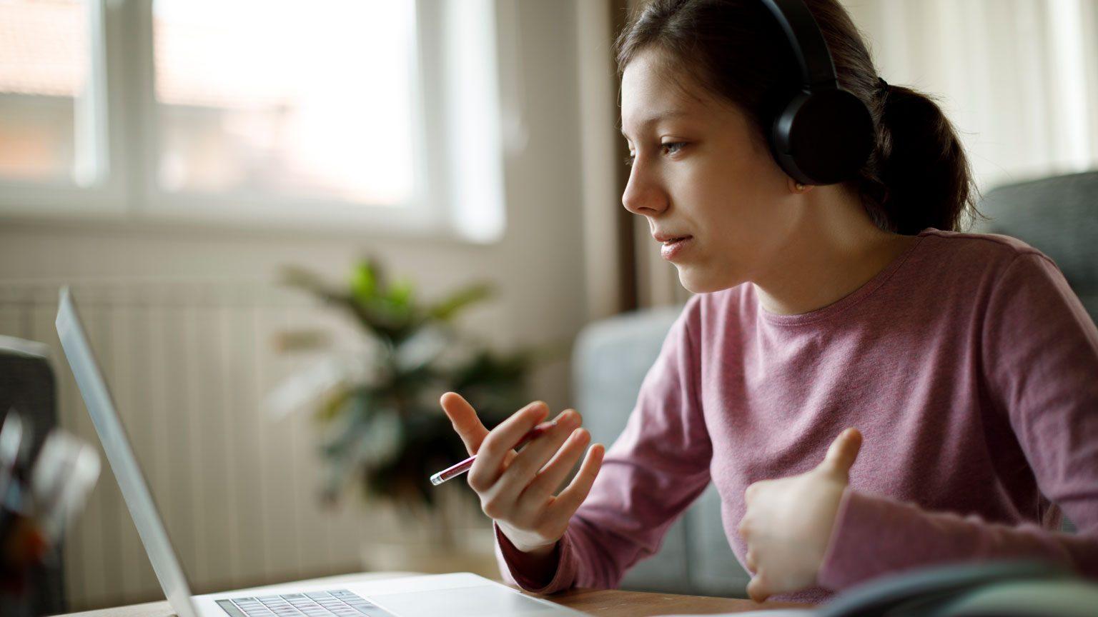 Teenage girl with headphones having online school class at home
