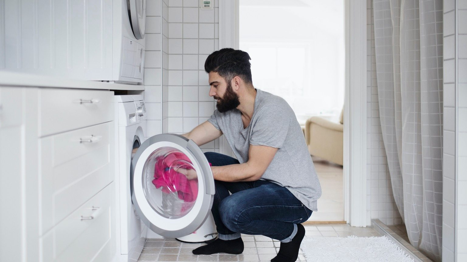 man crouching while loading clothes in washing machine at home