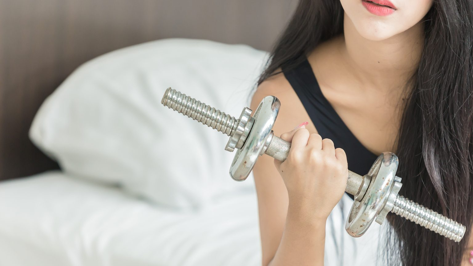 Woman with dumbbell at home