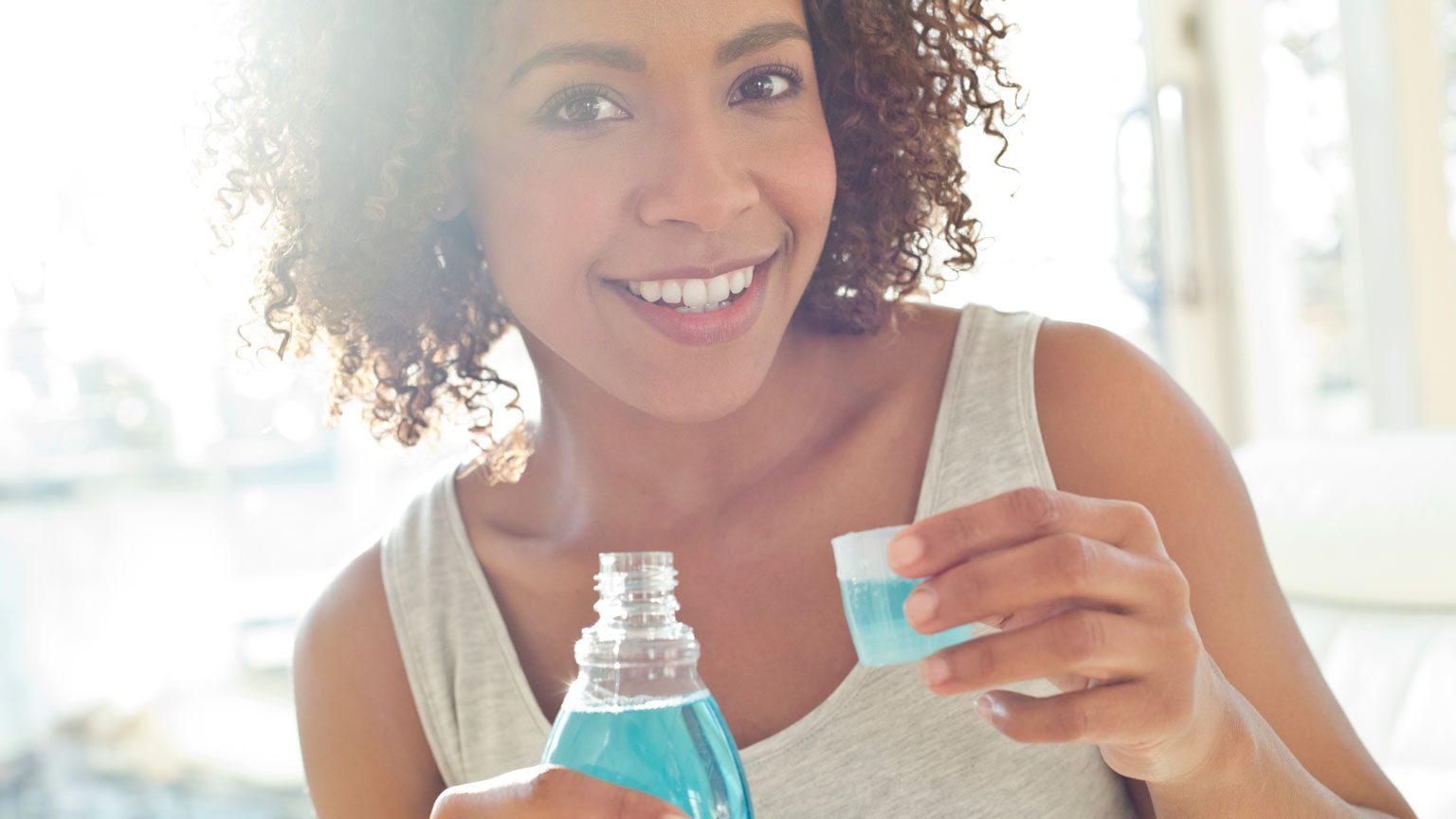 Portrait of woman using mouthwash