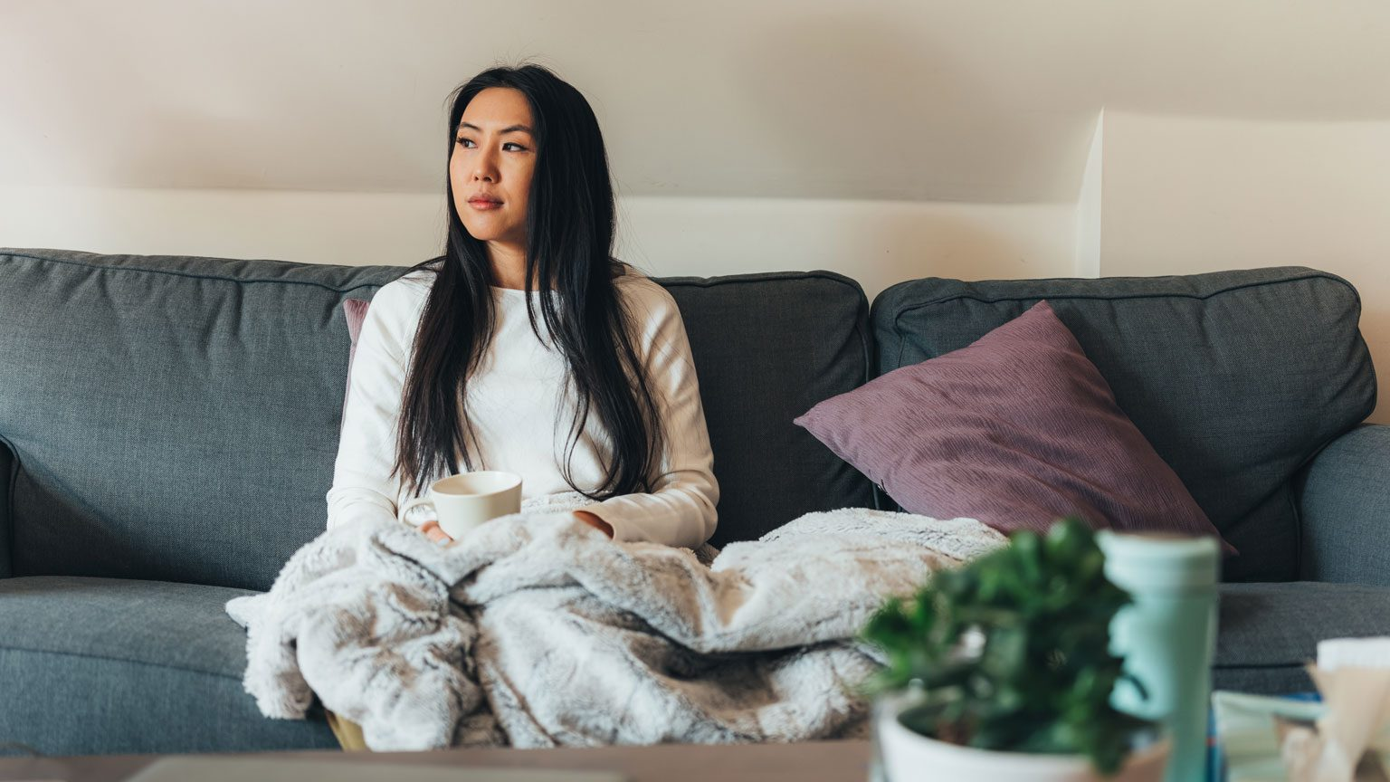Asian woman feeling sick with flu, fever and headache while at home.