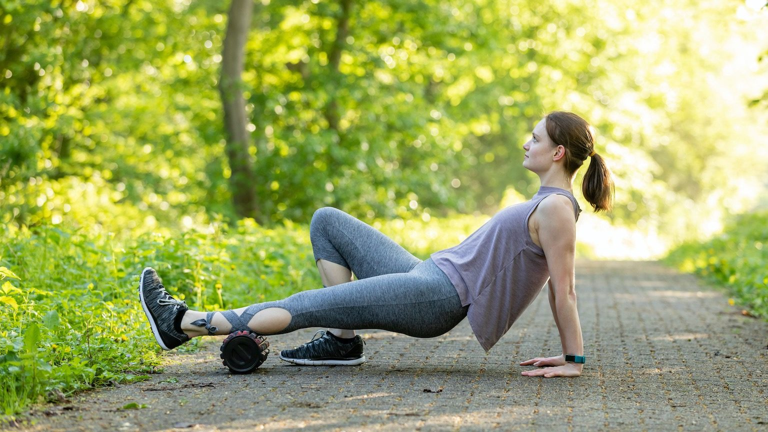 Young woman is doing fitness with a blackroll in nature