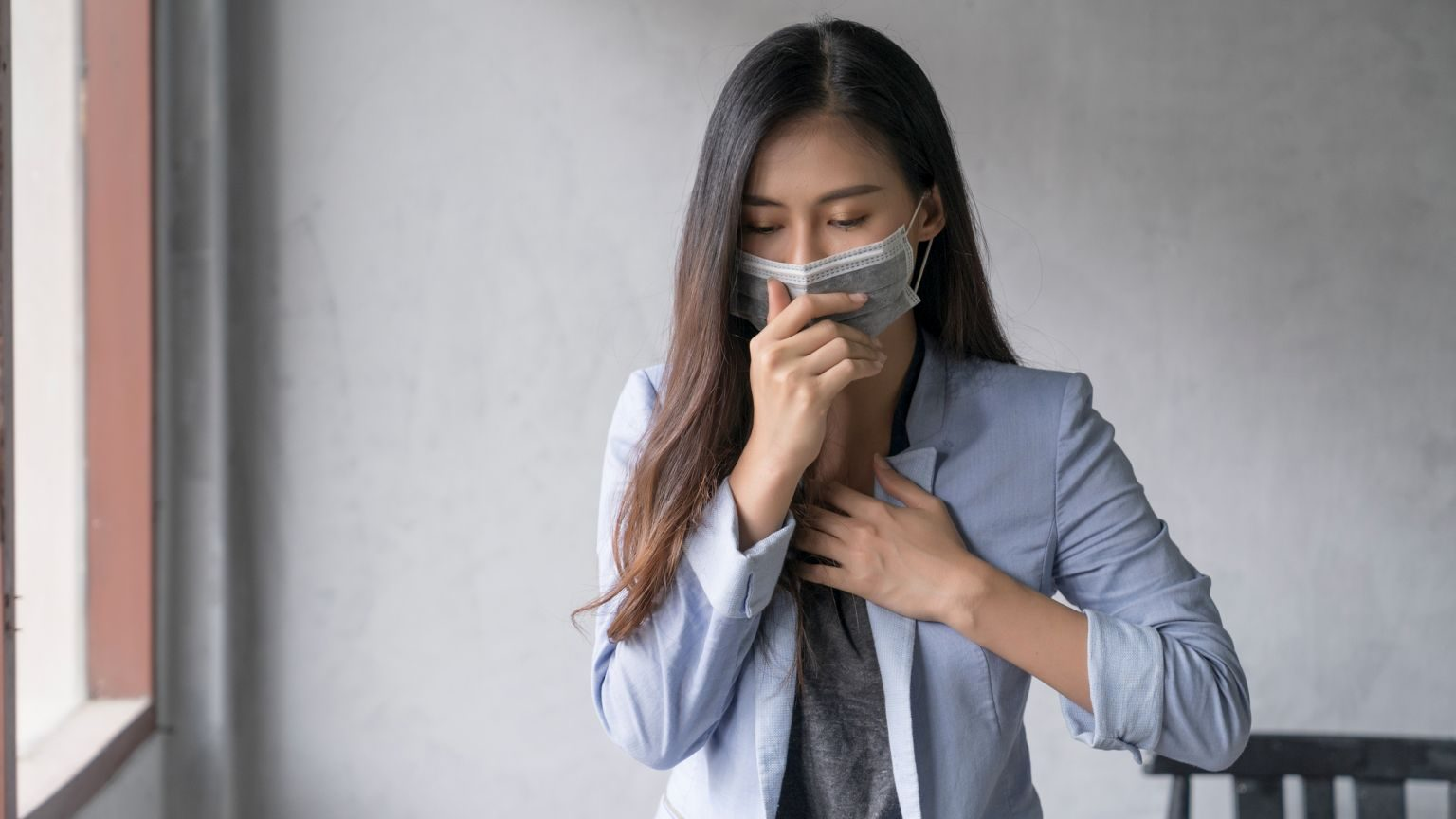 Business woman wearing face mask and cough influenza while working in office