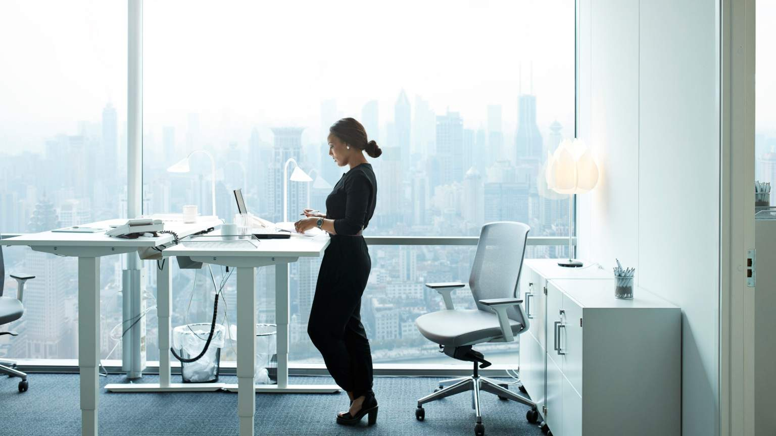 Elegant businesswoman working alone with laptop in office building