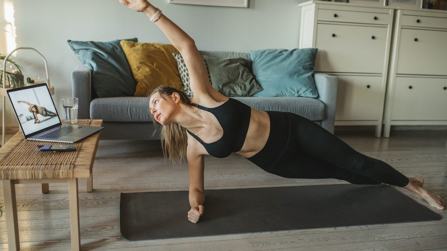 Lady doing pilates at home in lounge room while watching an online workout.