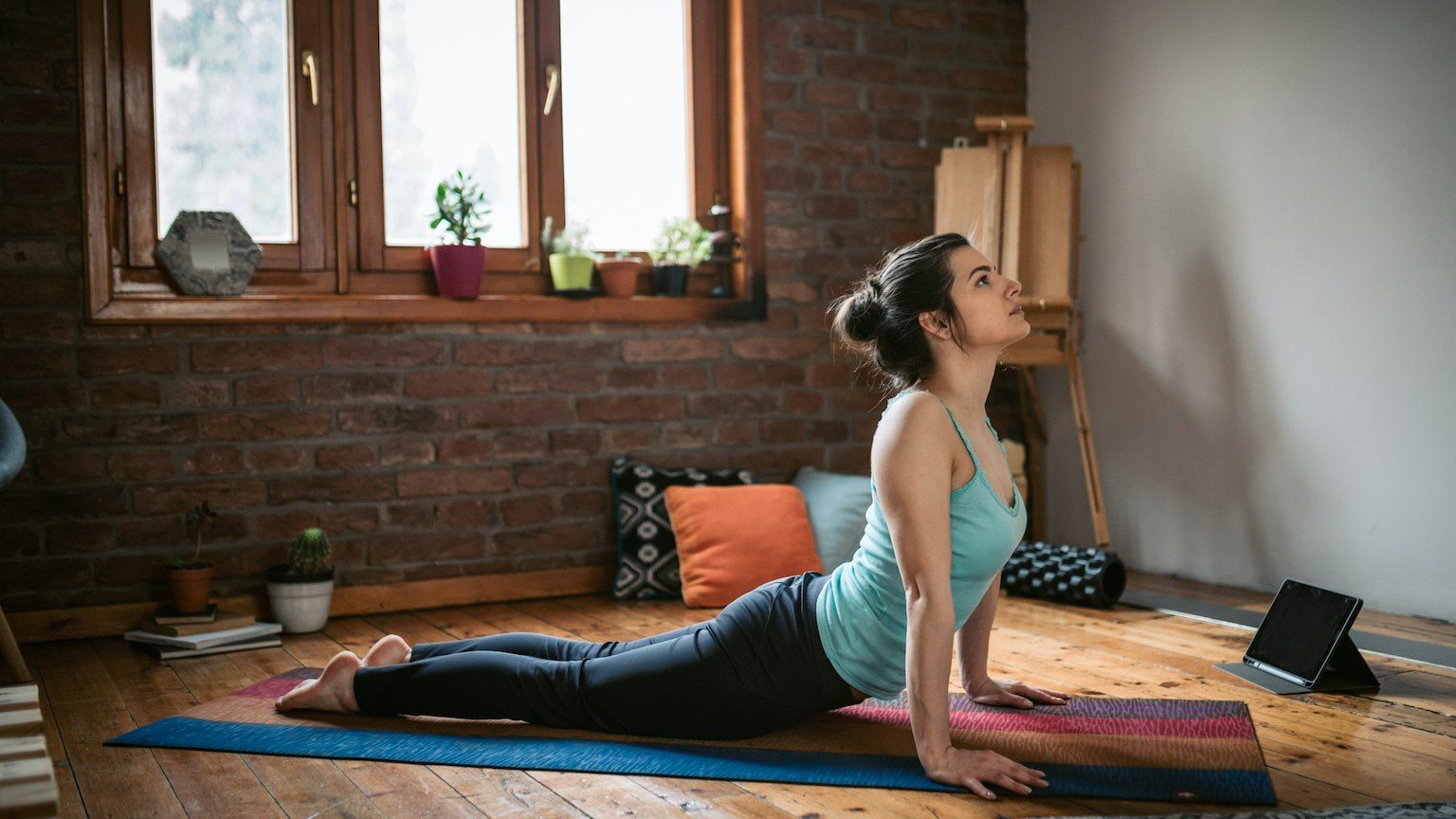 Lady stretching on pilates mat at home.