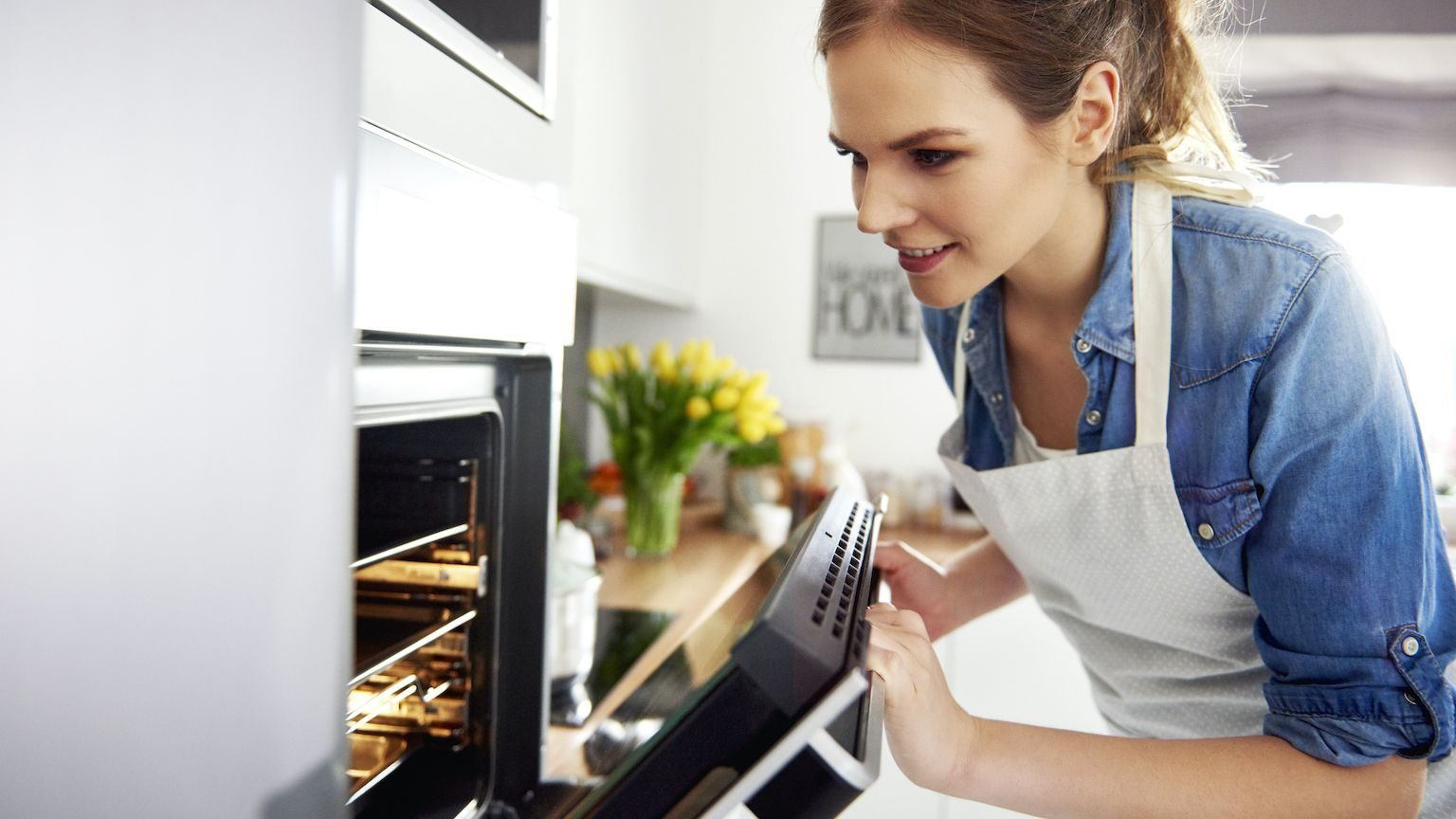 Young woman wearing a white apron peering into an oven
