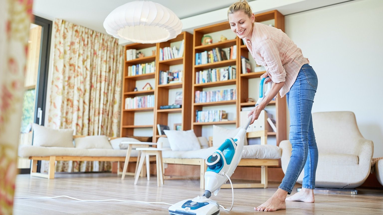 mother cleaning the floor with a steam mop