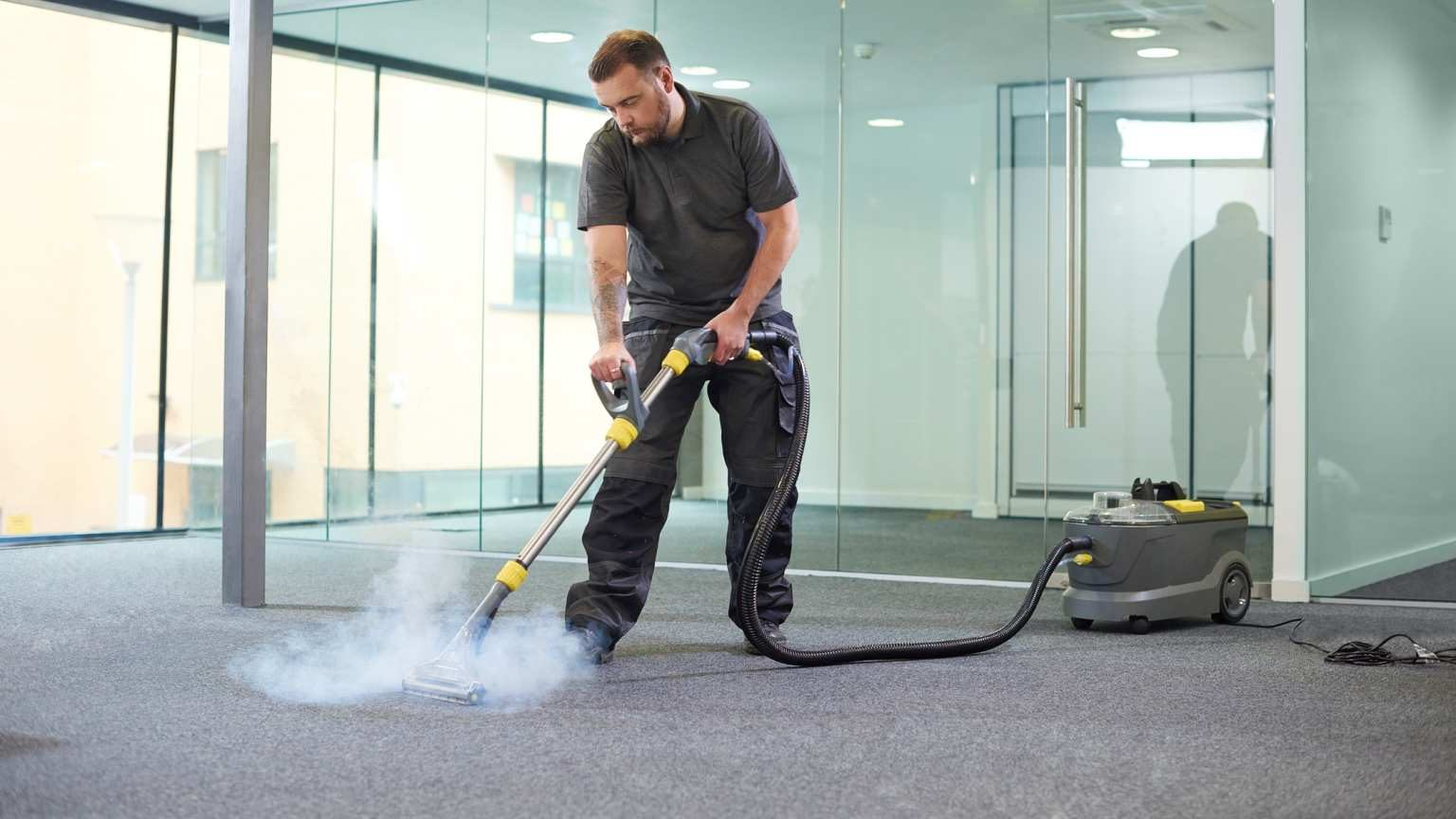 a male cleaning contractor steam cleans an office carpet in a empty office in between tenants.
