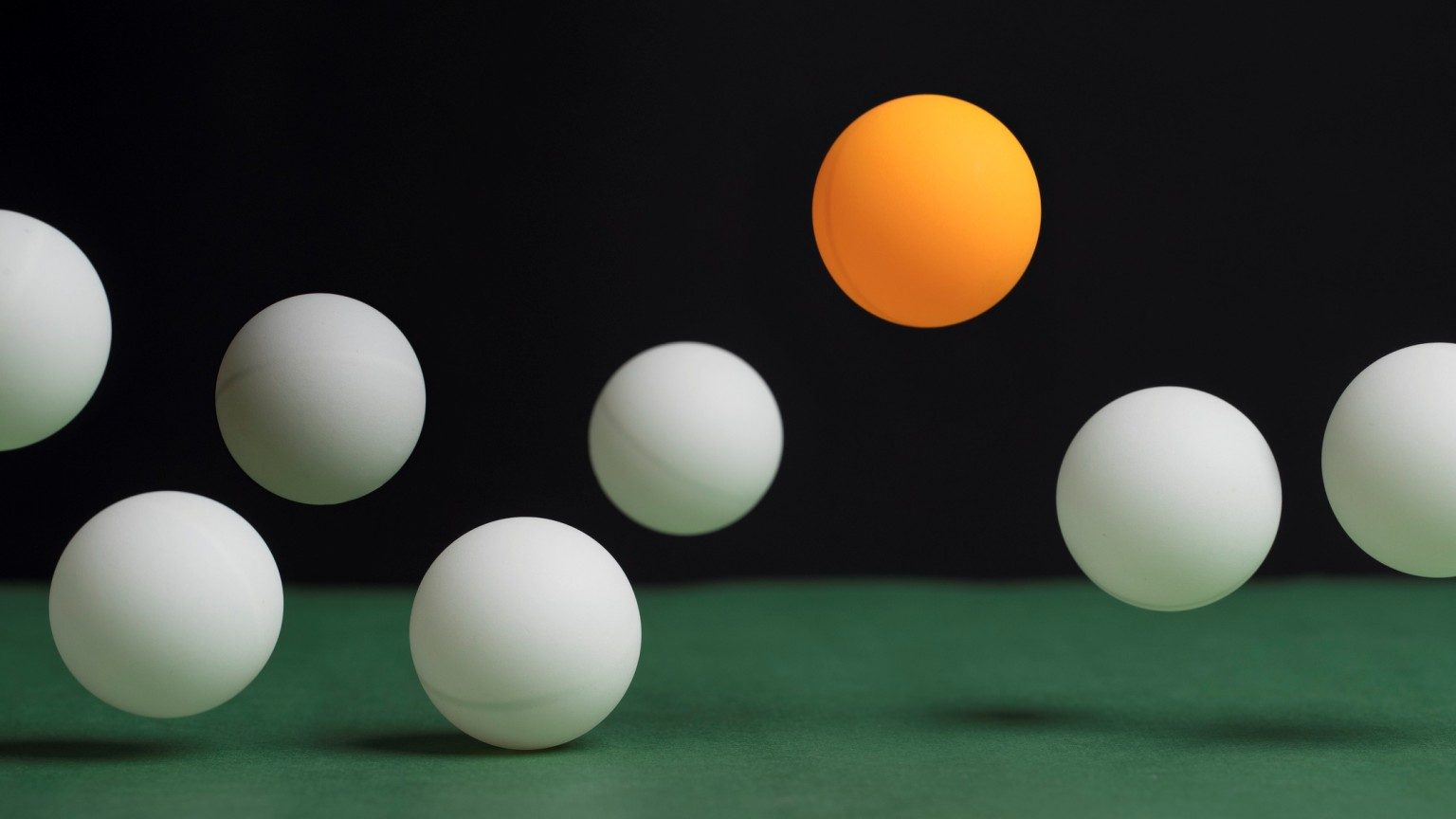 Group of Table Tennis Balls bouncing. The One orange ball is higher than the white balls.