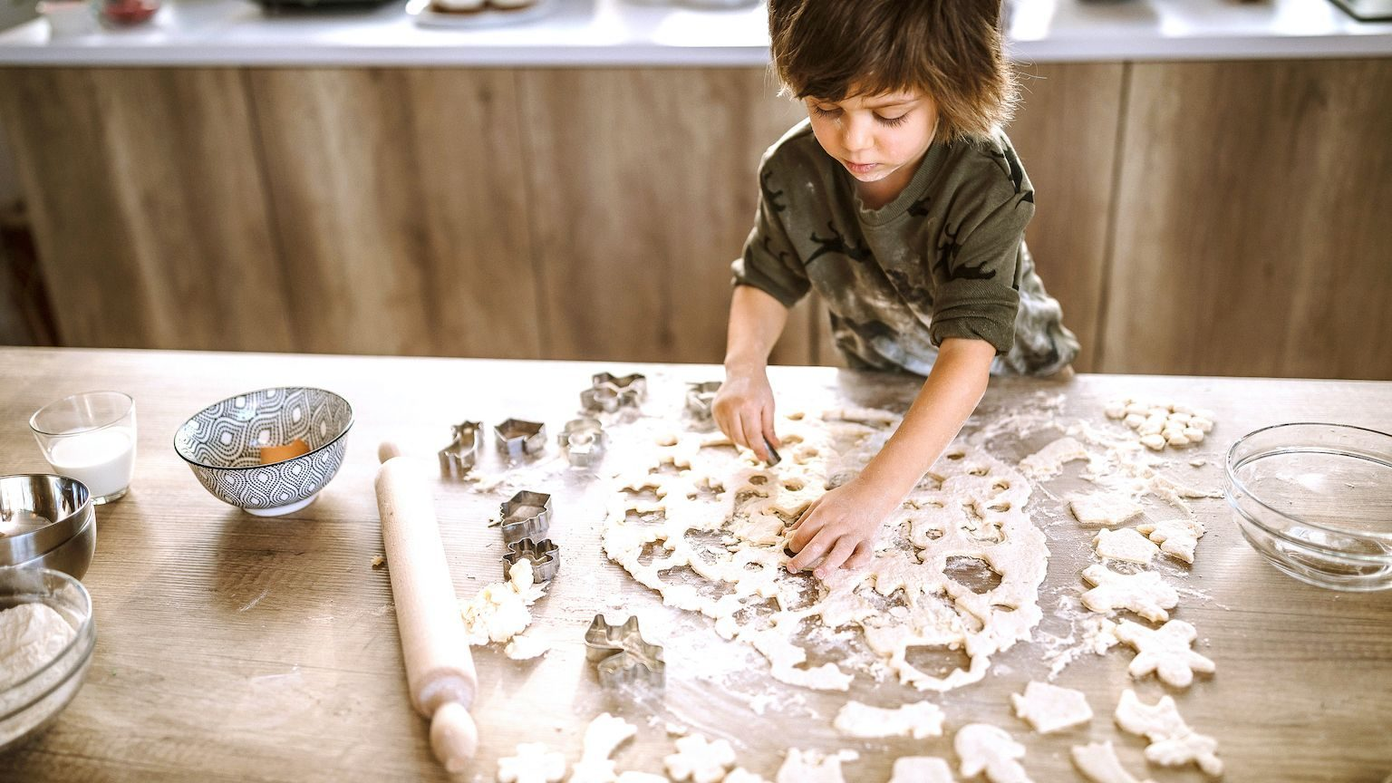 A young boy shaping cookies with a cookie cutter