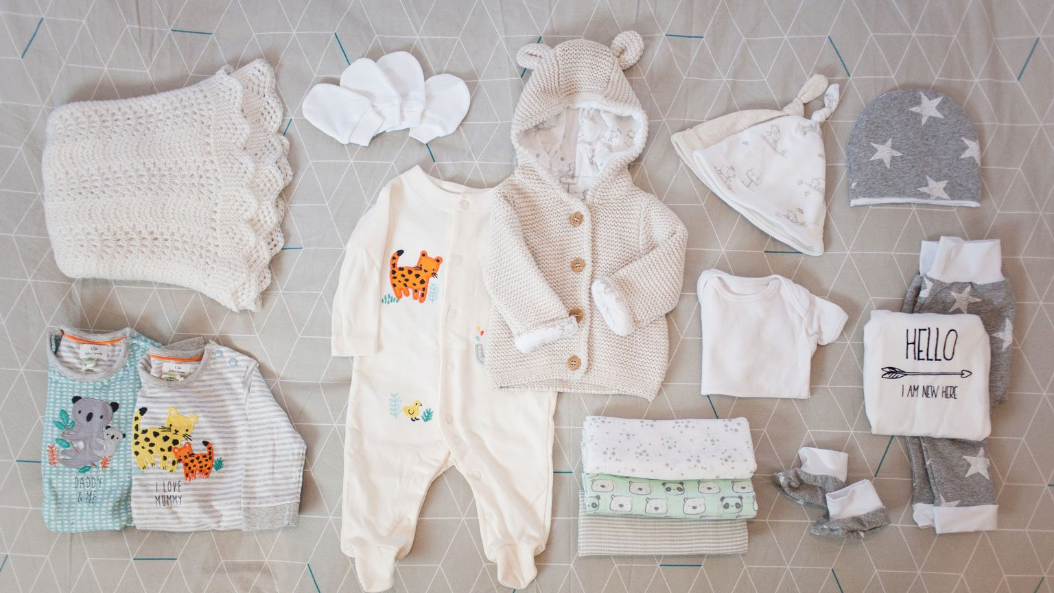 An example of some items new parents may pack in their hospital bag for the delivery of their new baby - blankets, clothes, muslins, scratch mittens, hats and booties.