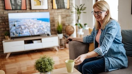 Mature woman drinking coffee at home and watching TV