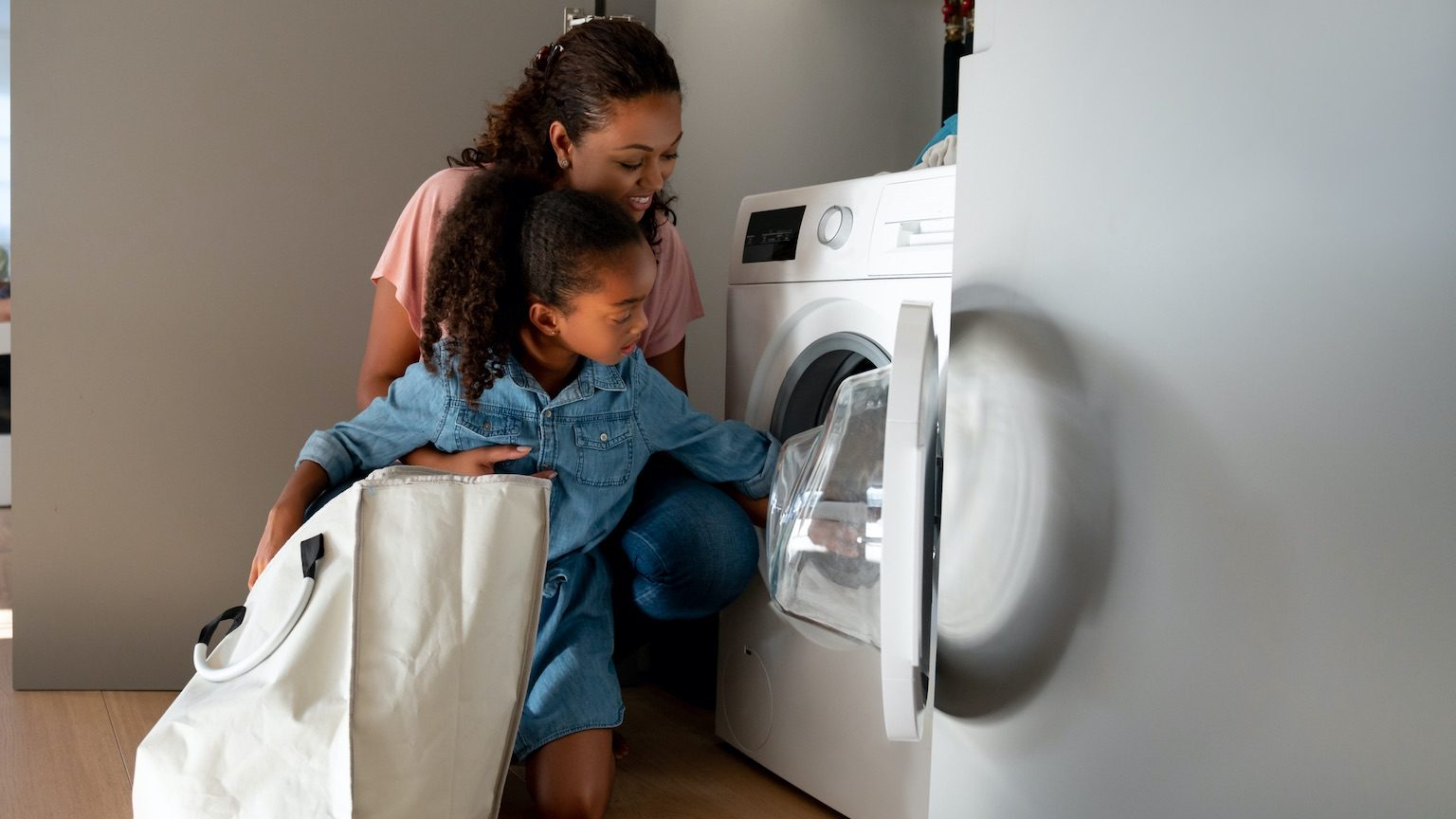 Happy mother teaching her daughter how to do the laundry at home