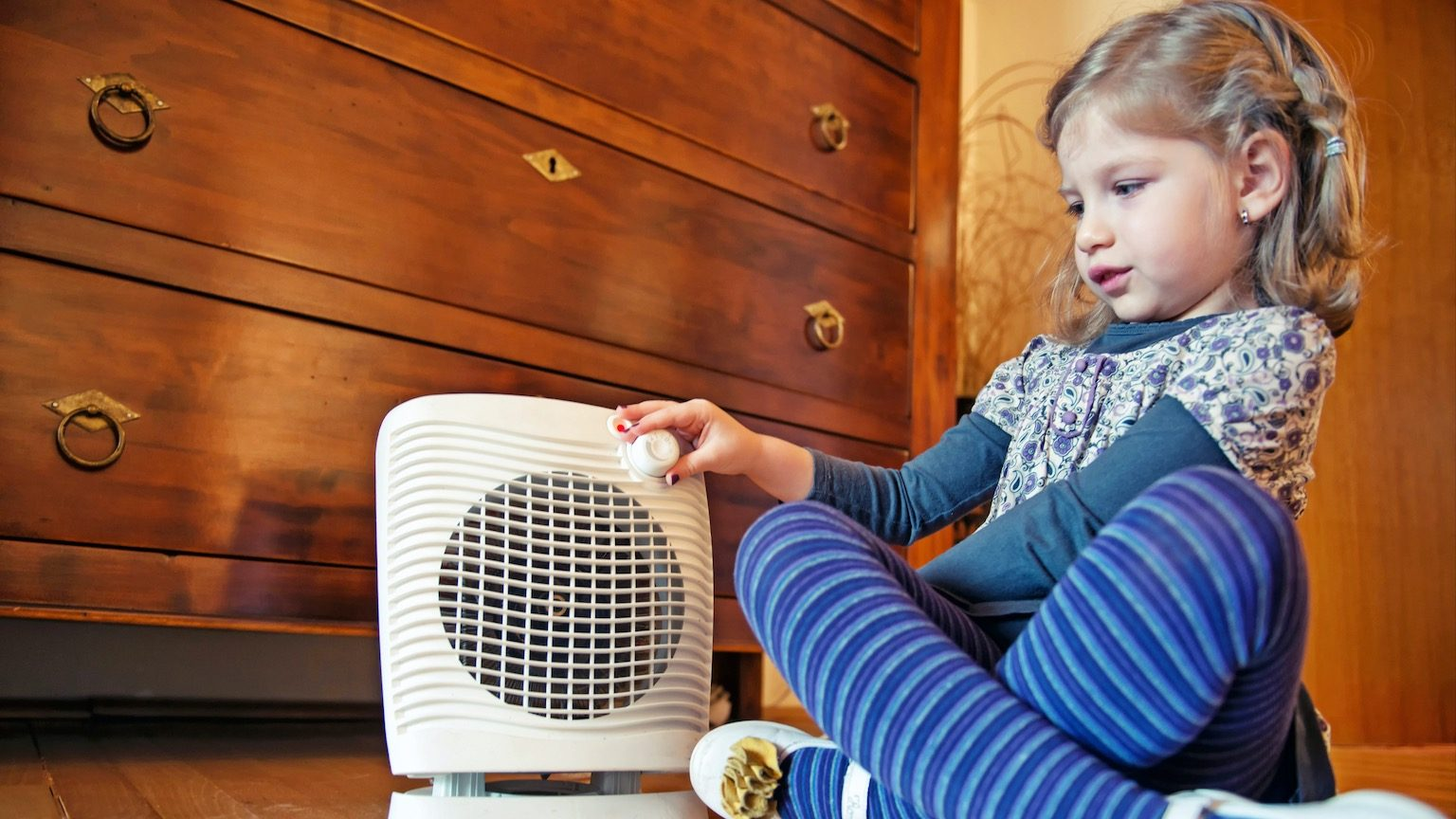 Image of a 5 years old girl sitting on floor and turning a fan heater off