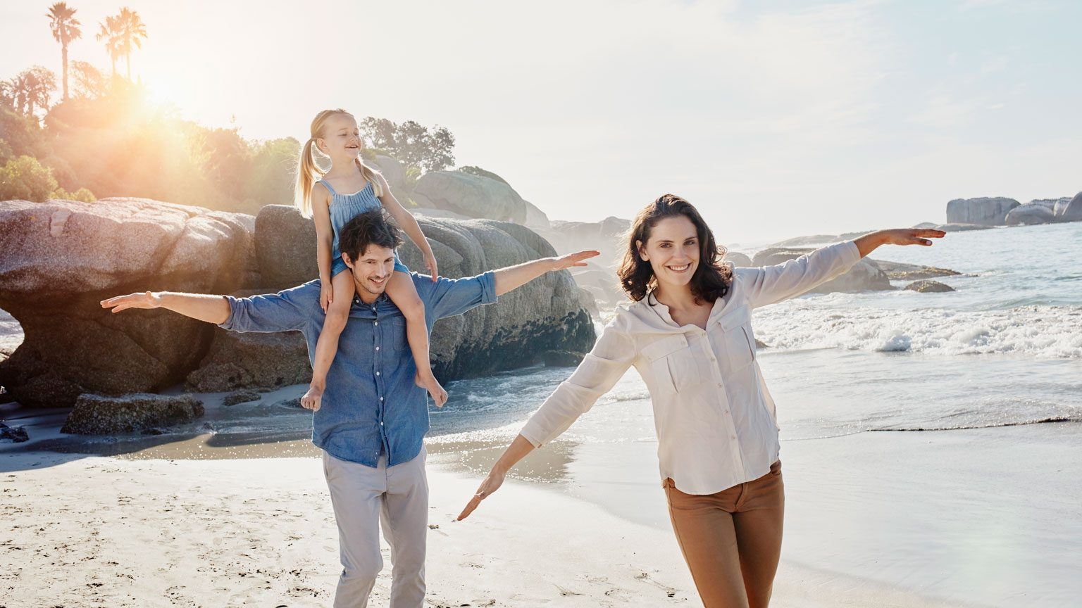 Happy family with daughter on the beach