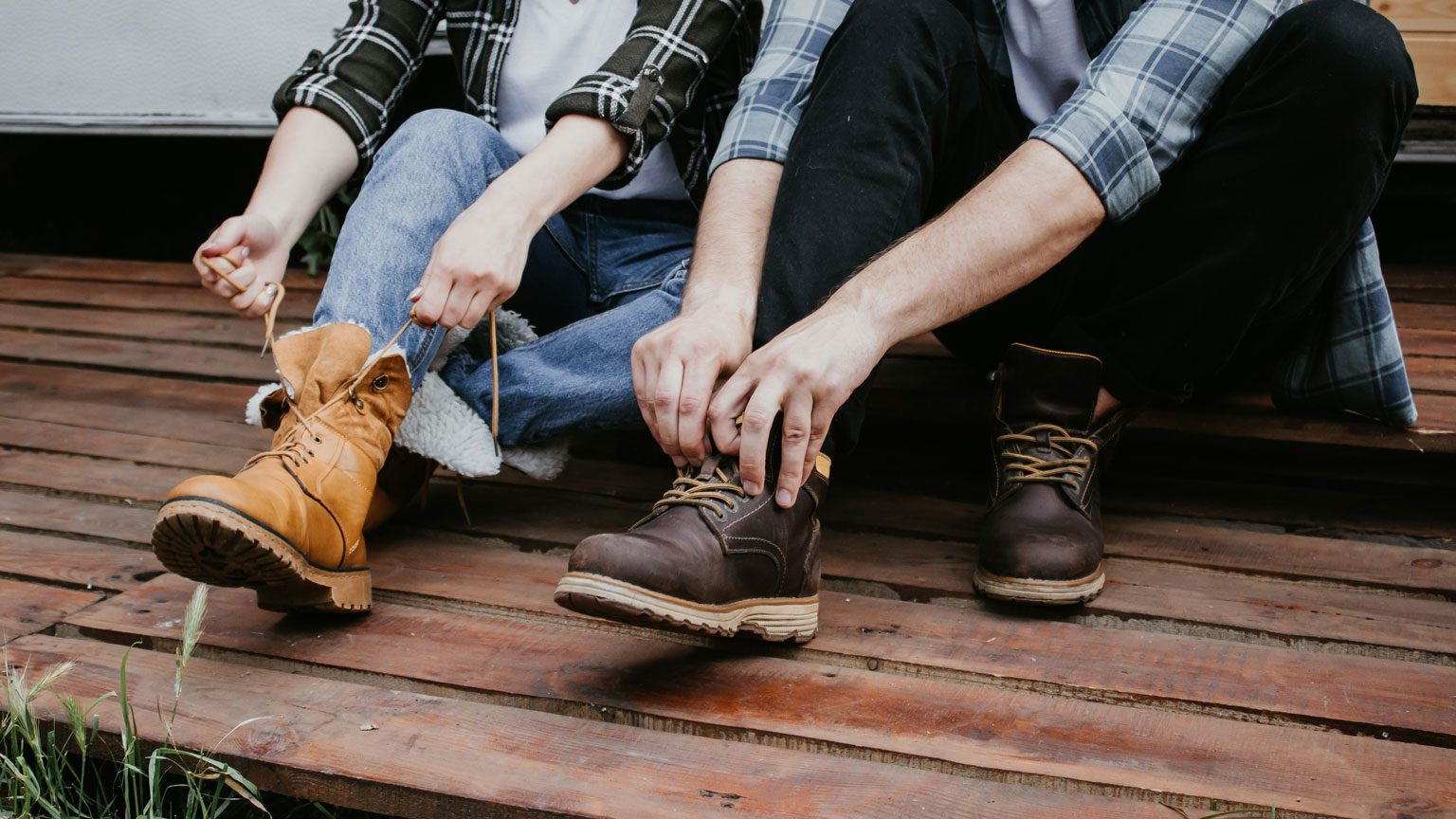 Young fashion man's and woman legs in blue jeans and brown boots on wooden floor