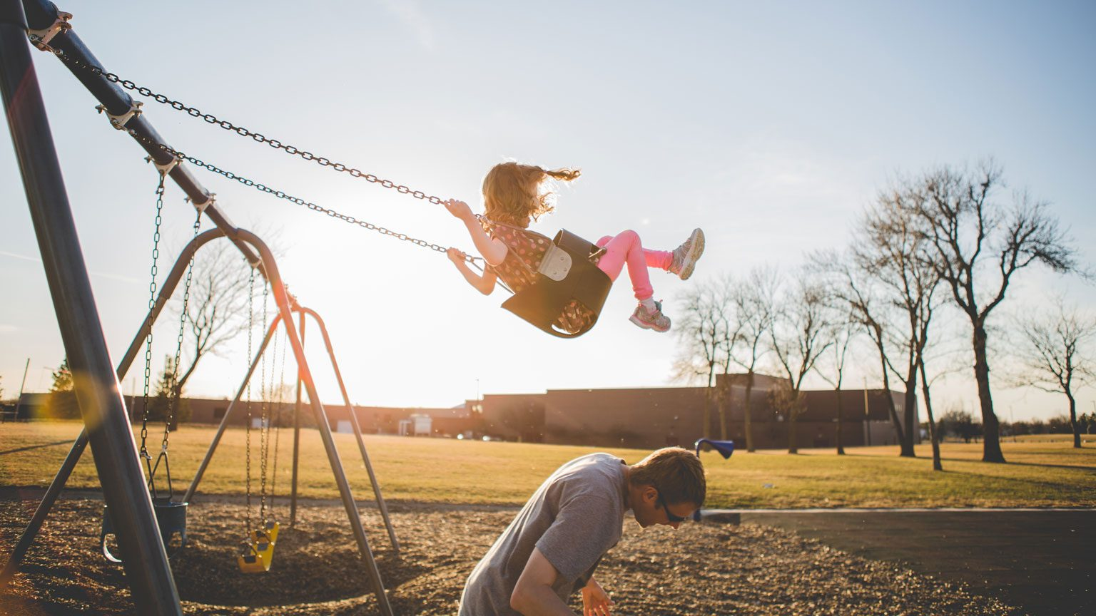 Man ducks bellow his daughter as he gives her a big push on a public park swing set