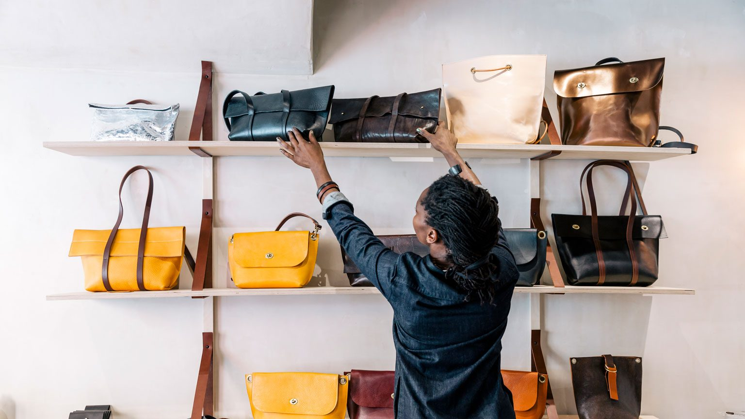 An entrepreneur handbag designer arranges her goods inside her store.