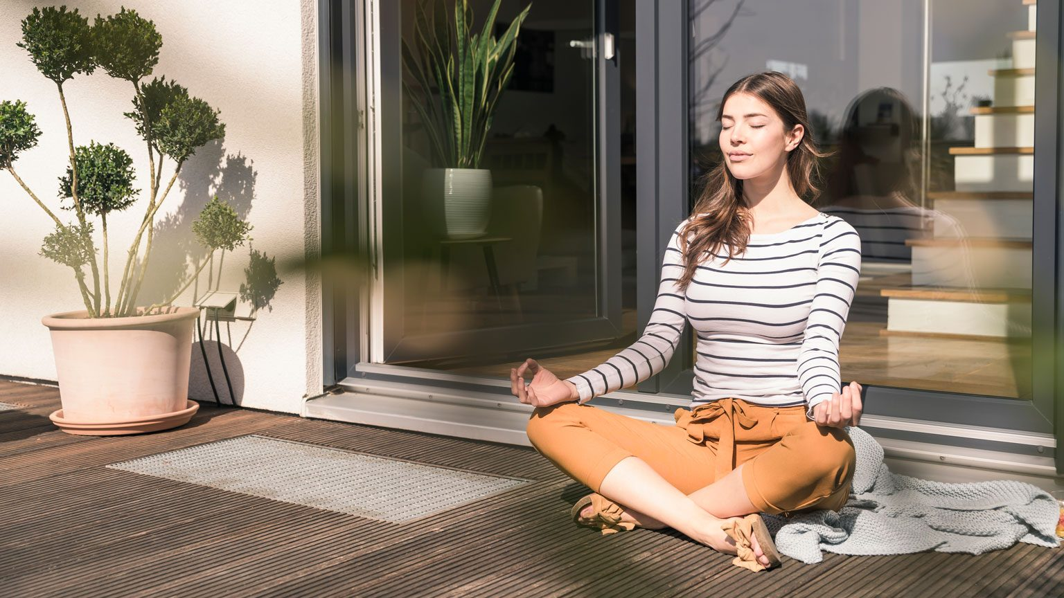 woman sitting on terrace at home practicing yoga
