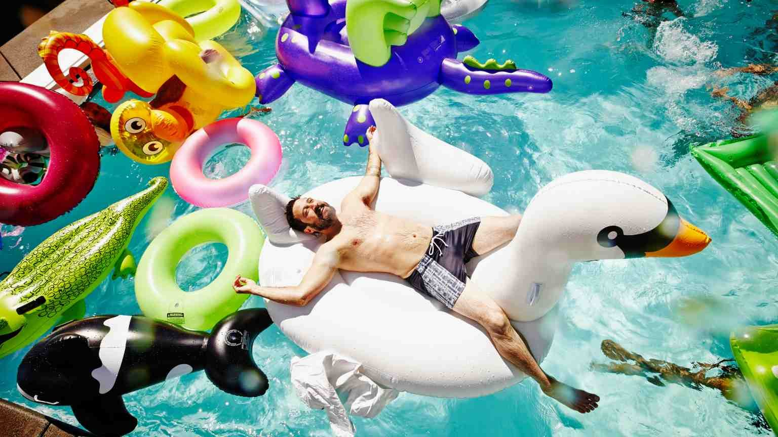 Smiling man relaxing on large inflatable swan in outdoor pool filled with multiple pool toys and friends swimming in background (Smiling man relaxing on large inflatable swan in outdoor pool filled with multiple pool toys and friends swimming in backg