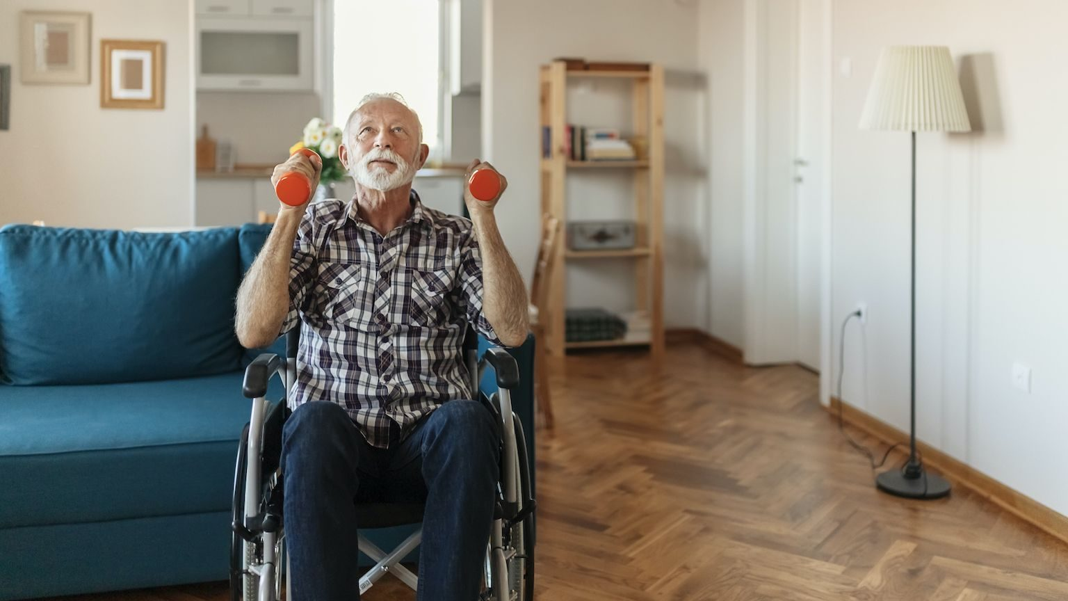 Older man in a wheelchair using weights to exercise